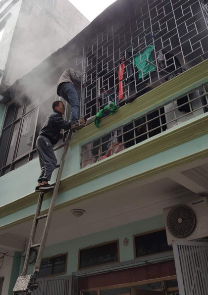 Người dân phố Cao Thắng, phường Yết Kiêu, Hà đông, bắc thang phá chuồng cọp ở căn nhà bị cháy. Ảnh: Kienthuc.net.vn.
