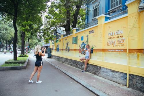 Khách du lịch nước ngoài thích thú chụp ảnh bên những bức tường được khắc họa độc đáo.