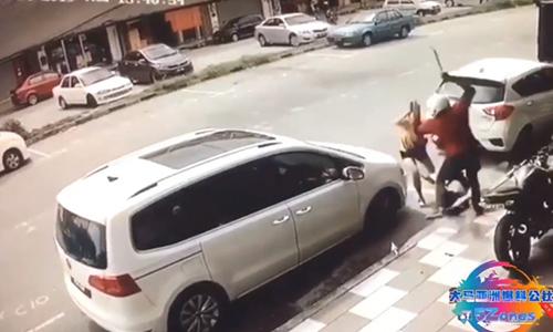 Cô vợ Malaysia lao ra đỡ nhát dao của người lạ vào chồng mình. Ảnh: