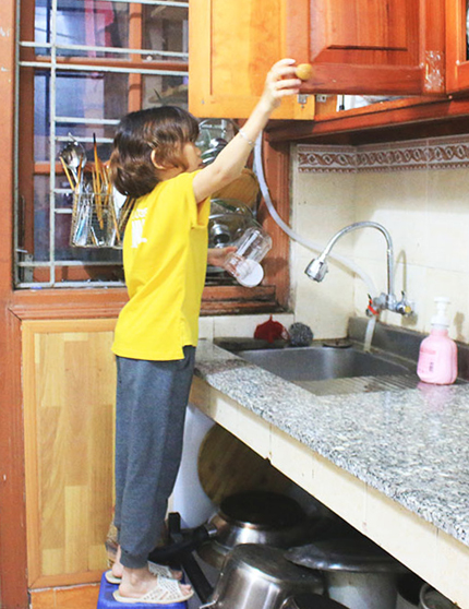 Khi nấu nướng, My phải đứng trên ghế mới có thể với tới bếp và chậu rửa. Ảnh: Hoài Nam.