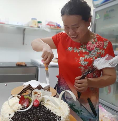 Chị Thanh nếm thử một sảnphẩm tại cửa hàng nhà mình. Chị từng nhận ra không thể bán báo dạo mãi nên quyết tâm theo đuổi nghềlàm bánh để chuyển hướng.Ảnh: Nhật Minh.