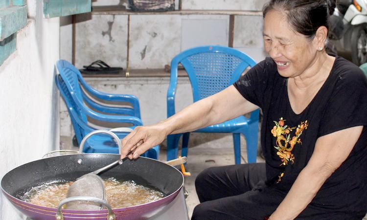 Bà Út Xuân, 59 tuổi, đang nấu món giả chay để ông Út Chứ đưa ra bệnh viện. Ảnh: Nhật Minh.