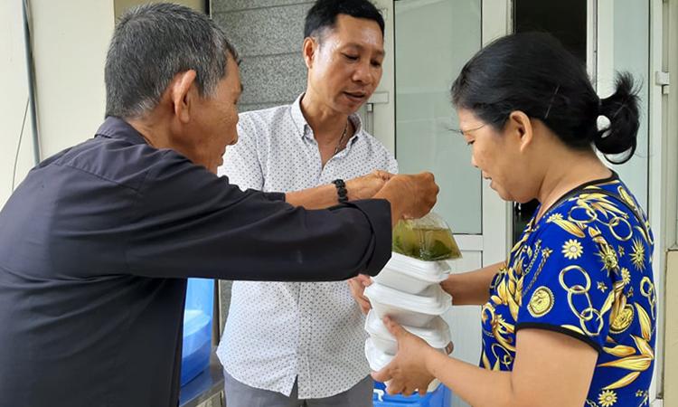 Ông Út Chứ cùng một mạnh thường quân đưa cơm đến bệnh viện phát cho từng người. Ảnh: Nhật Minh.