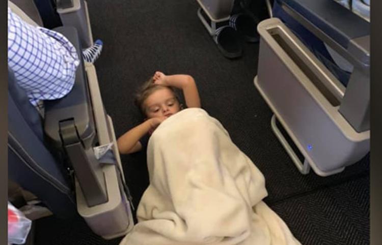 Bé Braysen nằm dưới sàn máy bay, đá vào hành khách nhưng mọi người đều vui vẻ. Ảnh: Facebook Cabriel.