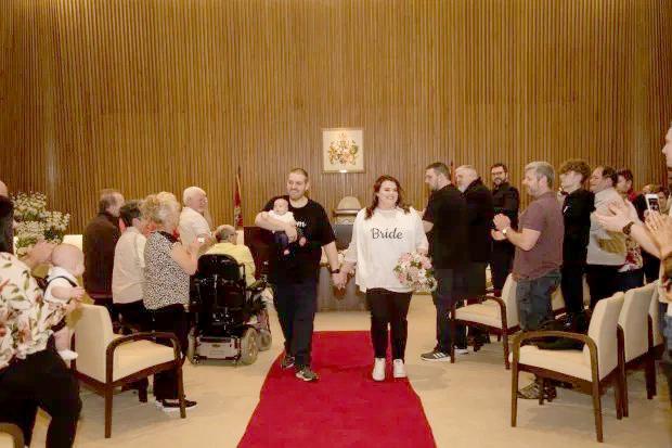 Hôn lễ tại tòa thị chính ở Darlington, cô dâu chú rể bế con theo, khách mời cũng mặc áo phông và quần jean giống cô dâu, chú rể. Ảnh: Kennedy News.