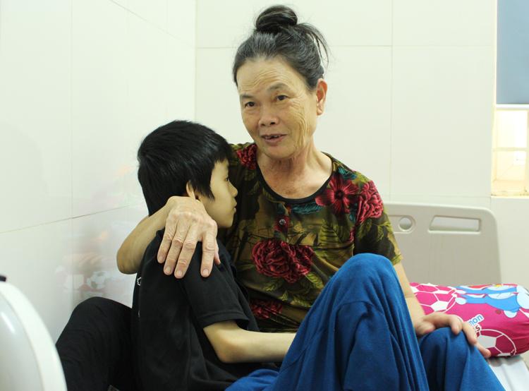 Nửa tháng qua, mặc kệcơn đau loét dạ dày của mình, bà Tám ở nửa viện tháng trời chăm cậu bé Long. Ảnh: Phạm Nga.