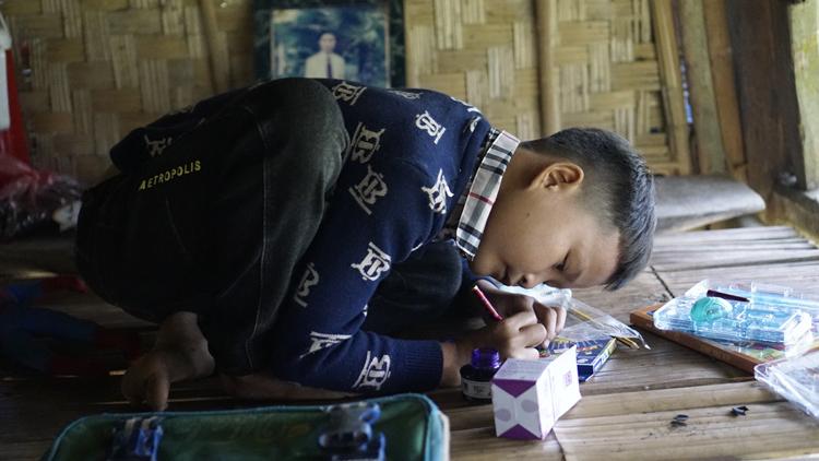 không có bàn, Khuyên học ngay trên sàn nhà. Cậu bé học khá, thích nhất môn văn. Ảnh: Trọng Nghĩa.