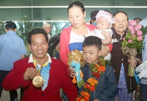 Lê Văn Công  bên gia đình, sau ngày nhận huy chương vàng giải vô địch cử tạ người khuyết tật thế giới năm 2016. Ảnh: Đức Đồng.