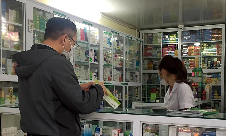 Một khách Trung Quốc mua khẩu trang tại tiệm thuốc ở phố Phạm Văn Đồng, Hà Nội. Ảnh: Phan Dương.