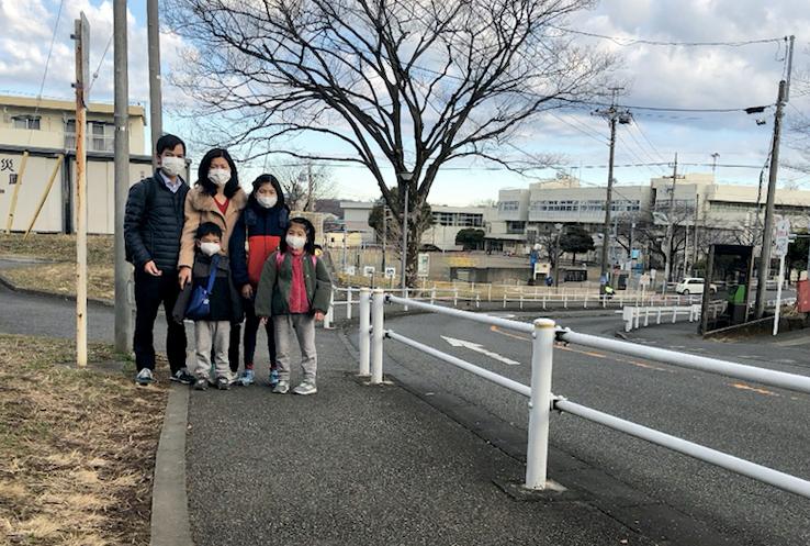 Gia đình anh Điển trước cổng trường tiểu học của các con, sáng 3/2. Ảnh: NVCC.