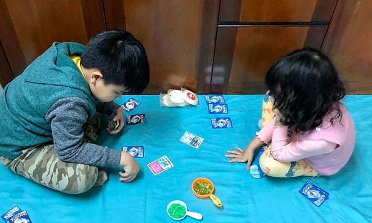 Hai con nhà chị Lệ Huyền tự chơi với nhau trò pokemon, phần thưởng dành cho người chiến thắng là 3 chiếc bánh gạo từ Tết. Ảnh: Huyền Đào.
