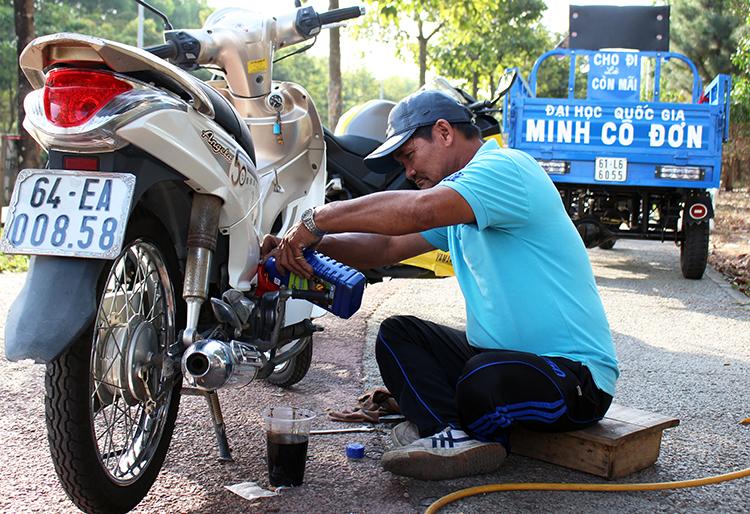 Ông Minh thay nhớt mới cho chiếc xe tặng bạn Trần Thị Hà, sinh viên trường ĐH Nông Lâm. Ảnh: Diệp Phan.