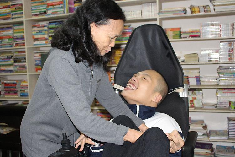 Từ khi sinh con, bà Sơn chưa một lần được đi du lịch cùng đồng nghiệp. Mọi sinh hoạt của con trai, đều một tay bà lo. Niềm vui của bà Sơn, là nhìn thấy nụ cười của con. Ảnh: Phạm Nga.