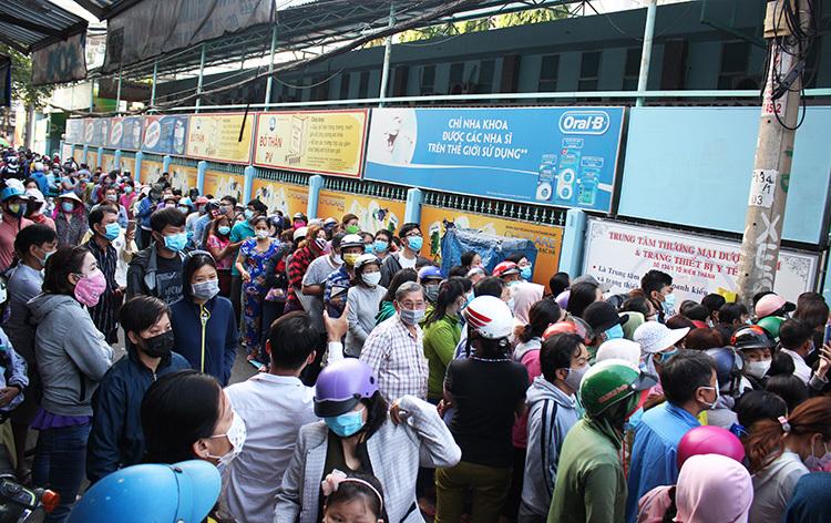 Hàng trăm người xếp hàng từ đêm để chờ mua khẩu trang. Ảnh: Phan Diệp.