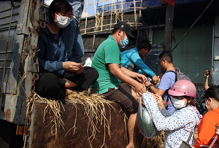 Dù được thông báo là dưa phát miễn phí nhưng nhiều người vẫn đưa tiền với mong muốn nhóm của chị Tưởng có thêm nhiều chuyến giải cứu giúp người nông dân Gia Lai. Ảnh: Diệp Phan.