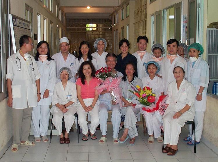 Y tá Nguyễn Thị Thục (người đầu tiên bên phải) cùng các đồng nghiệp chụp hình lưu niệm với bệnh nhân Sars, ông Hùng (ôm hoa hồng). Ảnh: Nhân vật cung cấp.
