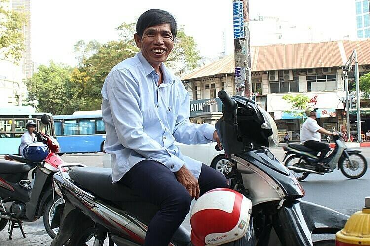 Ông Bình đậu xe trên vỉa hè đường Hàm Nghi, quận 1 chờ khách sáng 5/3. Ảnh: Diệp Phan.