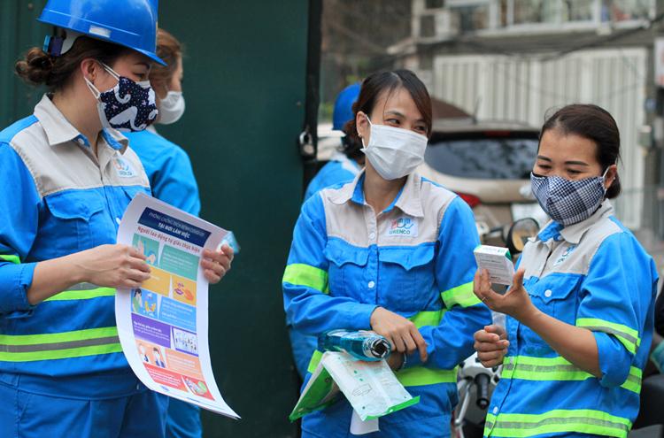 Công nhân môi trường tại phường Trúc Bạch nhận thêm đồ bảo hộ và hướng dẫn cách bảo vệ bản thân trong dịch corona, chiều tối 9/3. Ảnh: Phan Dương.