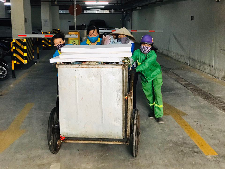 Mỗi lần đẩy xe rác lên khỏi dốc tầng hầm, chị Hạnh (ngoài cùng bên trái)cần phải nhờ thêm 3 người đẩy. Ảnh: Hải Hiền.