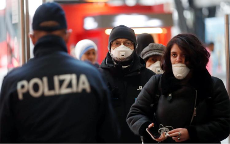 Cảnh sát và quân đội kiểm tra hành khách rời khỏi ga tàu ở Milan, Italy. Ảnh: AP.