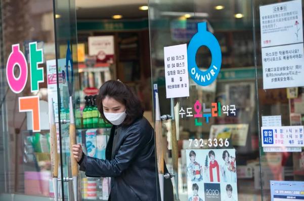 Một người phụ nữ đeo khẩu trang mua sắm ở Seol, Hàn Quốc. Ảnh: Bloomberg.