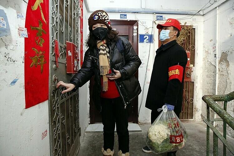 Những đảng viên cấp cơ sở đảm bảo thực phẩm, thuốc men cho người dân khi Vũ Hán phong toả.Ảnh: Xinhua.
