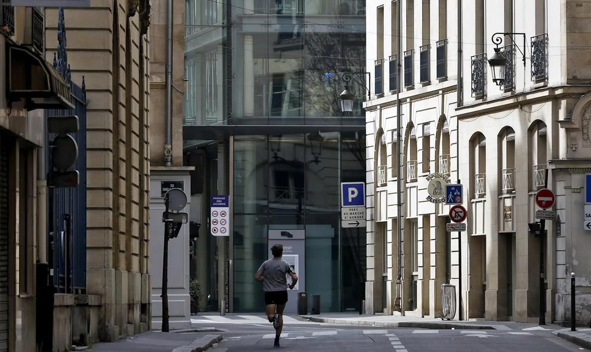 Một người đang chạy bộ trên đường phố vắng vẻ ở Paris trưa 17/3. Ảnh: AP