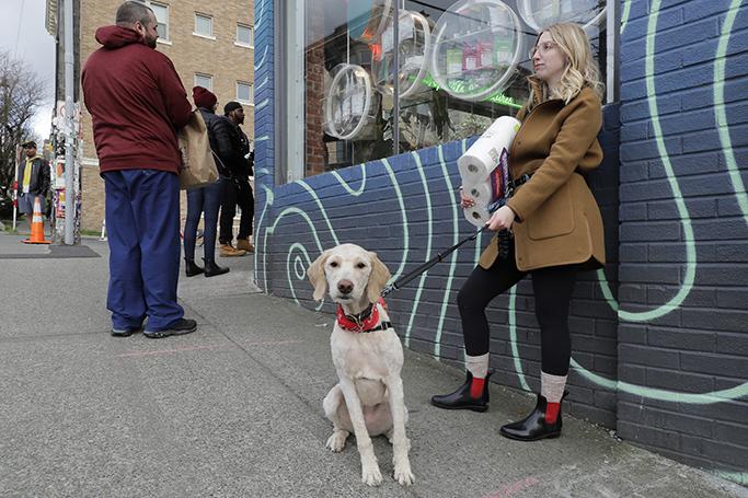 Mia Grace cầm một gói giấy vệ sinh khi cô và chú chó Breezy chờ bên ngoài một cửa hàng cần sa ở Seattle hôm 24/3. Ảnh: AP.
