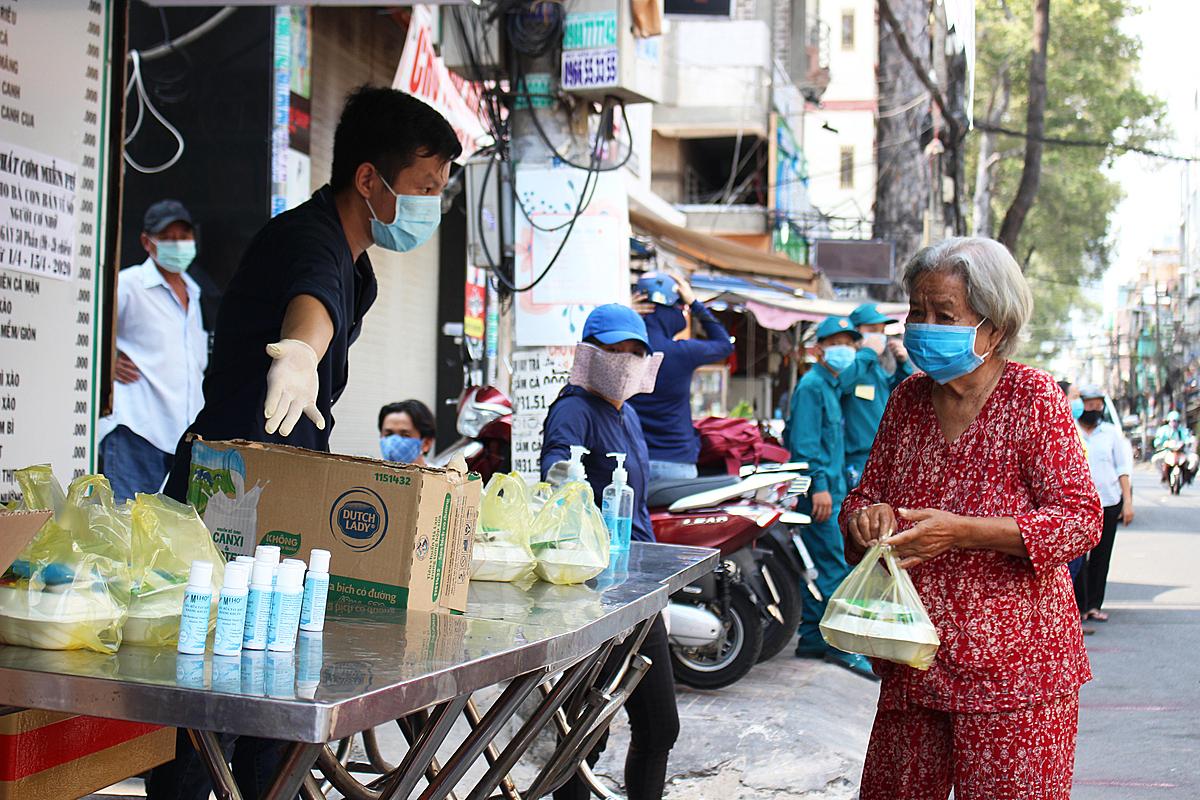 Ngoài một hộp cơm chayvà một hộp sữa, người dân còn được mạnh thường quân ủng hộ thêm nước rửa tay, người nào không có khẩu trang cũng sẽ được tặng. Ảnh: Diệp Phan.