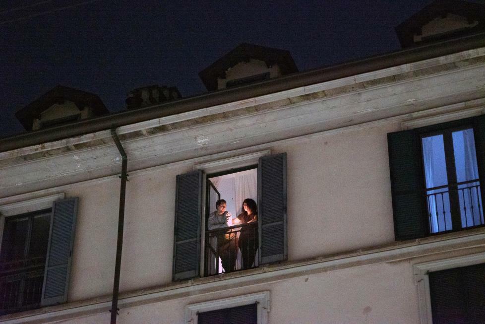 Cặp vợ chồng thắp nến, đứng ngoài ban công ở Milan, Italy, để động viên những người nhiễm bệnh. Ảnh: Nytimes.
