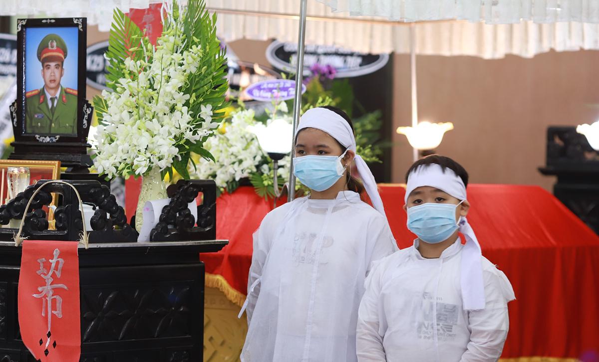 Hai con của thiếu tá Đặng Thanh Tuấn bên linh cữu cha, tại nhà tang lễ thành phố chiều 3/4. Ảnh: Nguyễn Đông.