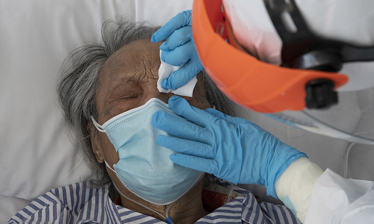 Các bác sĩ tại phòng chăm sóc đặc biệt Bệnh viện Nhân dân Đại học Vũ Hán chăm sóc cho bệnh nhân già mắc Covid-19. Ảnh: sohu.