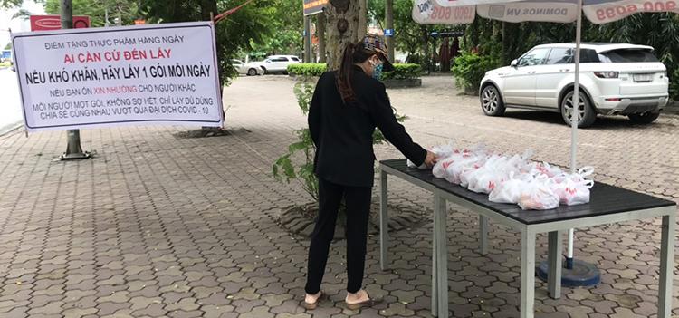 Cô Nguyễn Thị Hoa đến nhận phần thực phẩm tại điểm phát miễn phí trên đường Lê Văn Lương sáng ngày 9/4. Ảnh: Hải Hiền.